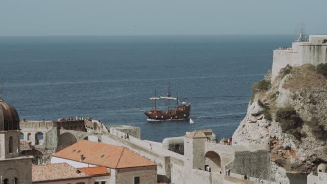 vidéos et rushes de bateau en bois karaka dans un port, fort lovrijenac, dubrovnik en dalmatie, croatie dans une journée ensoleillée, mouvement lent - navire