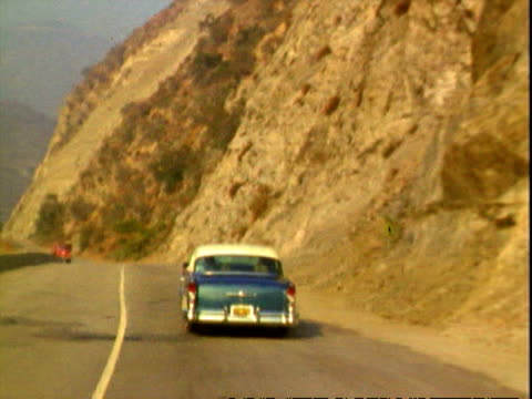 vidéos et rushes de entering angeles national forest / rear view subjective traveling shots of buick century driving along winding road snaking through valley, hazy... - 1950 1959