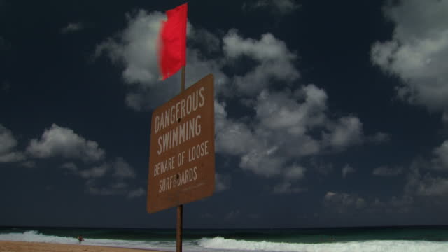wooden sign on beach with red wavy flag - turtle bay hawaii stock videos & royalty-free footage