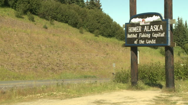 """wooden sign reading """"homer. alaska.  halibut fishing capital of the world."""" at side of sterling highway, visible with traffic passing both ways, upon entrance to homer, kenai peninsula, alaska."" - placard stock videos & royalty-free footage"