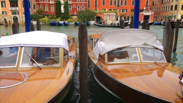 wooden speedboats moored along the grand canal in venice, italy, jib - barca a motore video stock e b–roll