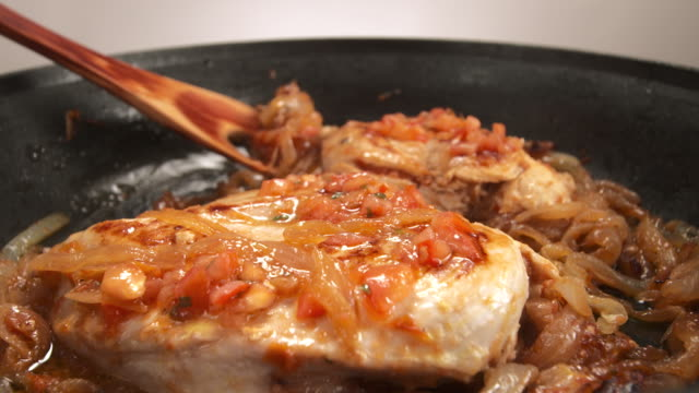 MS Wooden spoon spreading onions over cooked chicken breast in frying pan / Los Angeles, California, United States