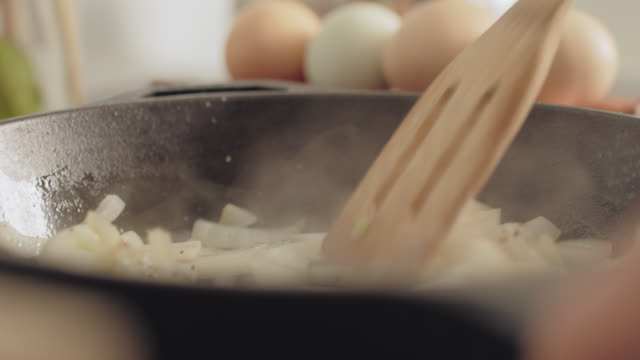 vídeos de stock, filmes e b-roll de cu wooden spoon stirs onions cooking in a pan - skillet cooking pan