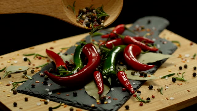 wooden spoonful of spices poured on hot peppers in slow motion - 赤唐辛子点の映像素材/bロール