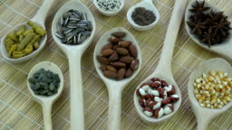 Wooden spoons with various vegetables, spice and nuts, rotating