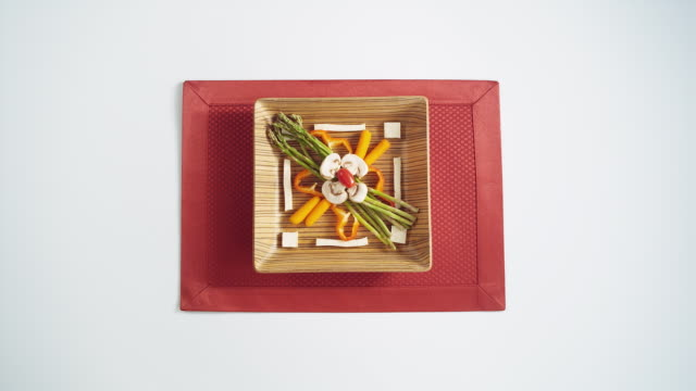 ms ha wooden square plate with vegetables and tofu artfully arranged being served onto red napkin - bamboo shoot stock videos & royalty-free footage