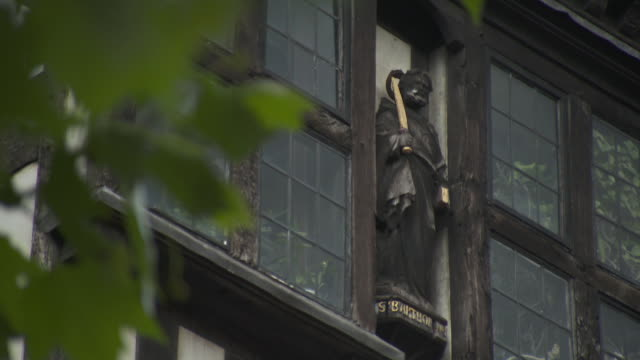a wooden statue of the apostle st bartholomew (st barthol) stands between two timber-framed windows in troyes, france. - xvii° secolo video stock e b–roll