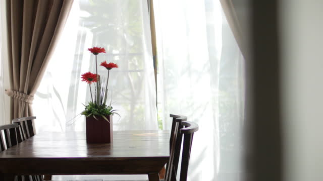 Wooden table in the morning with blur curtain window and green garden , Dolly shot right to left