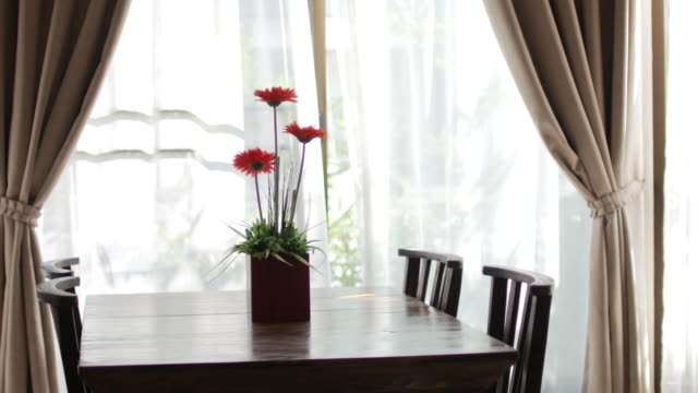 右から左に緑の庭、ドリーの花の花瓶のぼかしカーテンの窓と木製のテーブルを撮影 - リビング点の映像素材/bロール