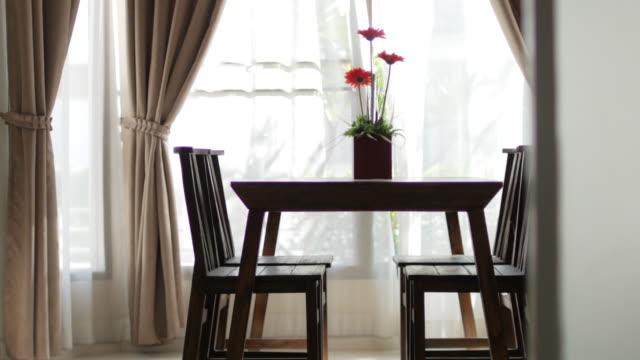 右から左に緑の庭、ドリーの花の花瓶のぼかしカーテンの窓と木製のテーブルを撮影 - 部屋点の映像素材/bロール