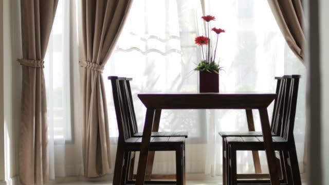 木材のテーブル花の花瓶にぼかし緑豊かな庭園とカーテンの窓 - リビング点の映像素材/bロール