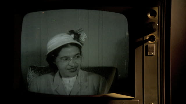 Wooden TV set in staged lighting MONITOR in 1956 Archival Playback w/ AfricanAmerican Civil Rights activist Rosa Parks seated in chair...