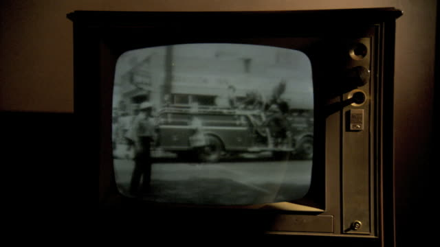 Wooden TV set in staged lighting MONITOR in 1960s Archival Playback w/ President John F Kennedy at desk AfricanAmerican Civil Rights protestors...
