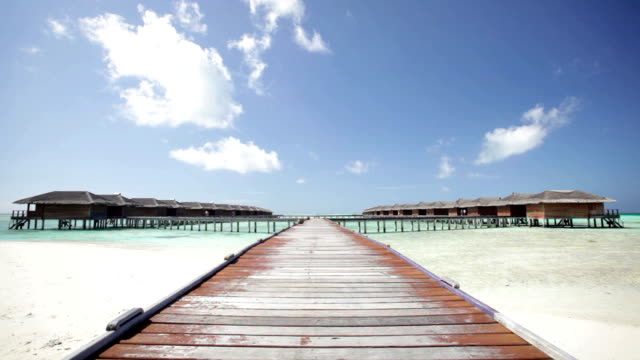 wooden walking path to water bungalows