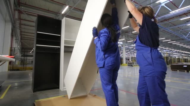 wooden wardrobe panels sit stacked on an automated roller belt inside the new ikea ab manufacturing plant in velikiy novgorod, russia on tuesday,... - employment issues stock videos & royalty-free footage