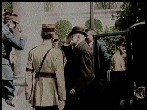 Woodrow Wilson and other politicians step out of cars and greet a crowd at Compiegne / A crowd gathers inside a large hall for the signing of the...