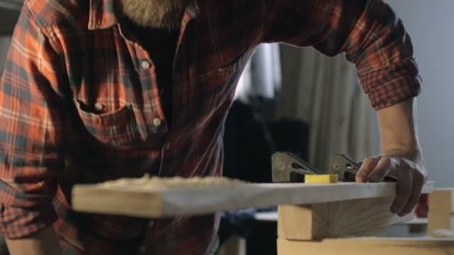 Woodworker blowing on wood shavings