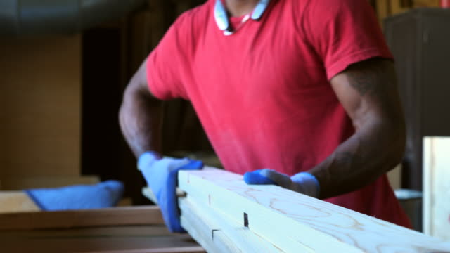 ts woodworker carrying stacks of lumber in woodshop - timber stock videos & royalty-free footage