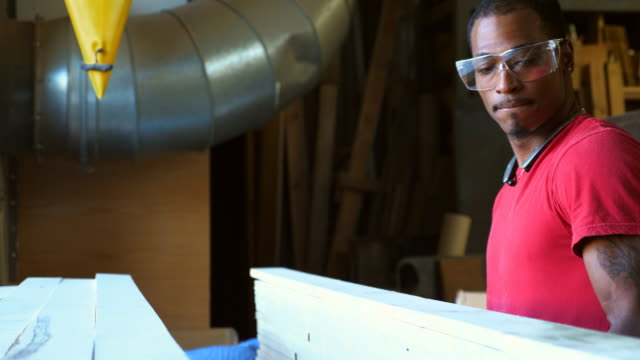 ms woodworker organizing stacks of lumber in woodshop - one mid adult man only stock videos & royalty-free footage