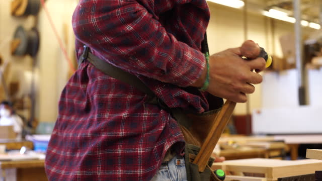 cu of woodworker putting hammer in tool belt - tool belt stock videos and b-roll footage