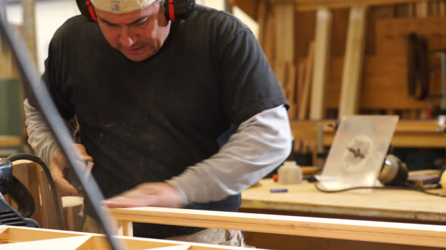woodworker sands custom window frame by hand in woodworking shop - window frame stock videos and b-roll footage