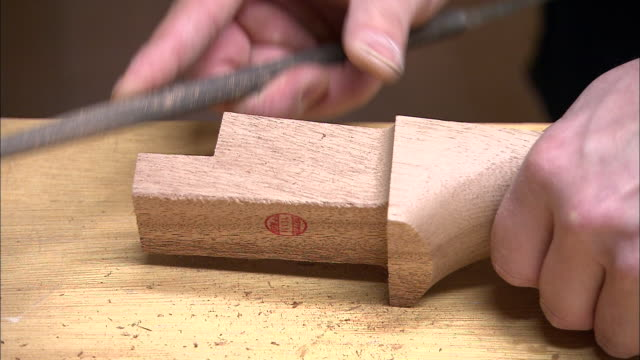 a woodworker smooths a piece of carved wood. - craft product stock videos and b-roll footage