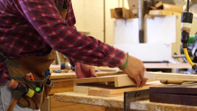 Woodworker tests interlocking cut wood pieces for proper fit