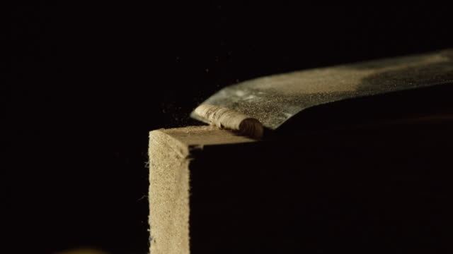 a woodworker uses a chisel along the edge of a red oak board against a black background - chisel stock videos and b-roll footage
