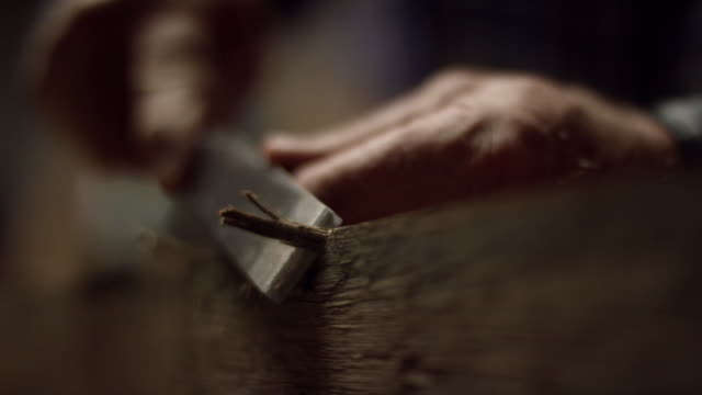 a woodworker uses a chisel along the edge of a red oak board - craftsperson stock videos & royalty-free footage