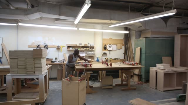 woodworkers operate sanders and assemble drawers and bedpieces at the urban green workshop in brooklyn new york thursday june 12 2016 shots wide shot... - workbench stock videos & royalty-free footage