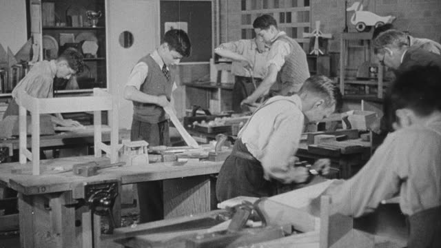 montage woodworking students making wooden toys in a classroom with the instructor observing / united kingdom - 作業場点の映像素材/bロール