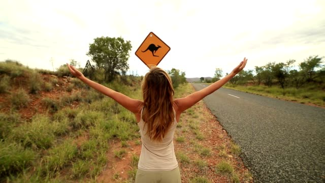 woohoo! girl arms outstretched in australia - road warning sign stock videos & royalty-free footage