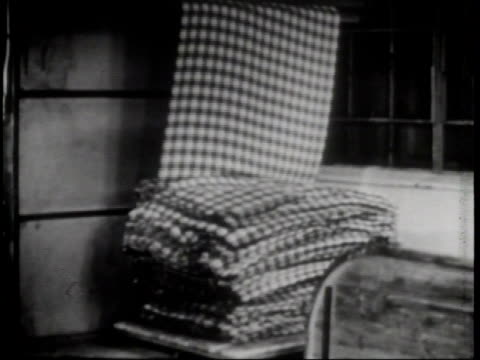 wool blanket folds as it comes out of machinery / a machine presses the material as its final step / children play on a swing set and jump rope in... - タータンチェック点の映像素材/bロール