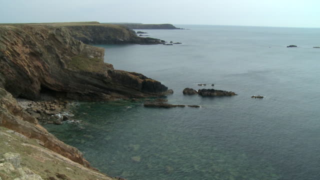 wooltack point, pembrokeshire, wales. pan left towards clifftops - bay of water stock videos & royalty-free footage