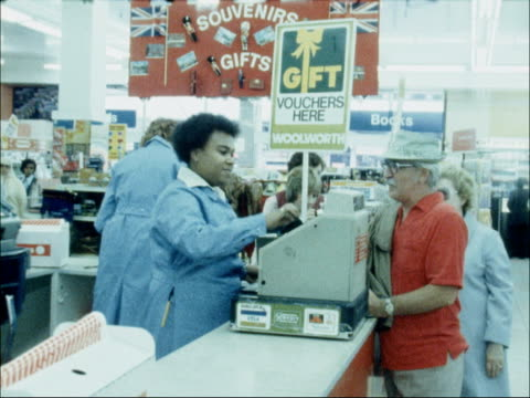 vídeos de stock, filmes e b-roll de woolworths announce drop in profits england london side cashier at till in woolworths store pull out as serves customer pan and zoom another cashier - woolworths