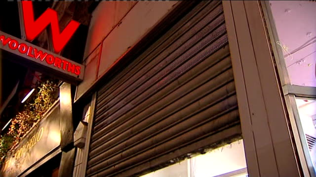 vídeos de stock, filmes e b-roll de woolworths stores close down / shoppers grab last minute bargains night woolworths employee closing down shutters on store for last time reporter to... - woolworths