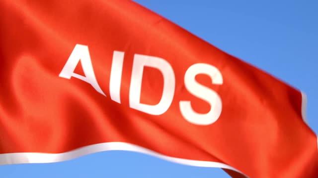 aids wort flagge winken in den himmel - geschlechtskrankheit stock-videos und b-roll-filmmaterial