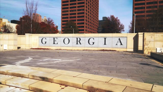 word georgia overlooking atlanta cityscape on the georgia state capitol grounds - georgia stati uniti meridionali video stock e b–roll