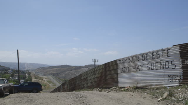 vídeos de stock e filmes b-roll de words written on mexican side of border wall translating to there are dreams on this side, too, wide-shot - muro circundante