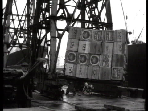 work and industry clip reel: part 1; tx 4.5.1961 and nr: dockers go back: b/w dockers outside / dockers working on unloading and loading inside - b rolle stock-videos und b-roll-filmmaterial