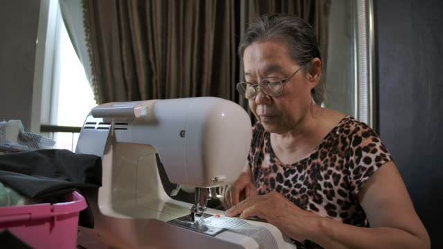 work at home concept, asian elderly women sewing the fabric with an automatic sewing machine - needle plant part stock videos & royalty-free footage