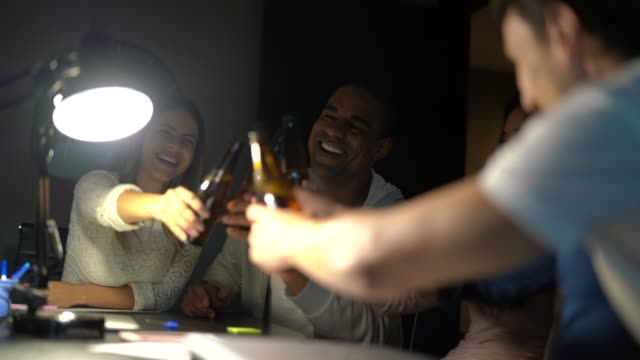 work colleagues toasting with beers on the office at night - beer bottle stock videos and b-roll footage