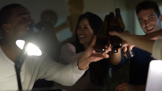 vídeos de stock e filmes b-roll de work colleagues toasting with beers on the office at night - 25 29 anos