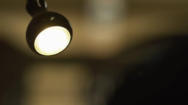 vídeos de stock e filmes b-roll de a work light shines on sawdust particles in the air - flutuar no ar