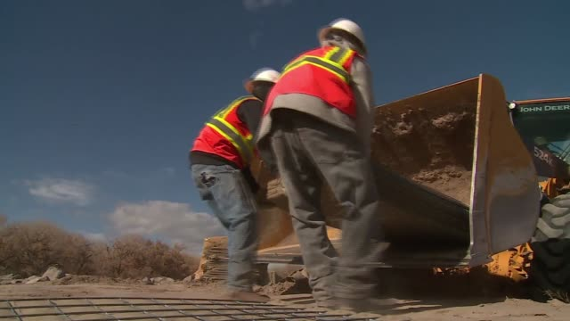 work men unload and build baskets for berms to protect against rain and flooding on indian reservation - puebloan peoples stock videos & royalty-free footage