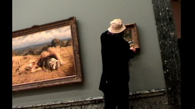 work of graffiti artist banksy goes up for auction tx banksy disguised as an old man hanging his ersatz old master painting 'crimewatch uk has ruined... - バンクシー点の映像素材/bロール
