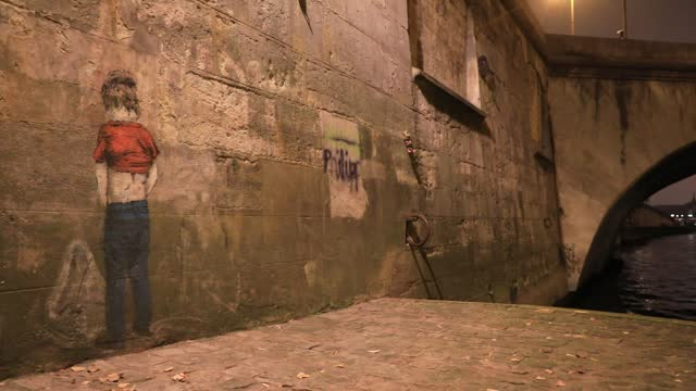 work of street art on seine river banks represents a child urinating on a wall as another lockdown continues to slow the spread of coronavirus during... - kind pinkelt stock-videos und b-roll-filmmaterial
