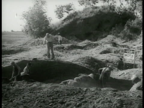 work program sign carpenters hammering on wooden frame at construction site men digging large hole men using horses to pull supplies in open pit... - 雇用促進局点の映像素材/bロール