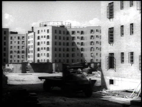 1939 ws work truck driving away from housing project under construction in harlem / new york city, new york, usa - 公営アパート点の映像素材/bロール