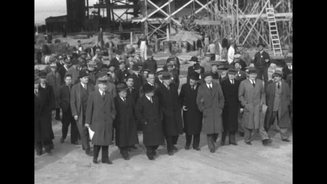 Work trucks driving towards construction site / three shots of NYC Mayor Fiorello La Guardia and group of officials walking along looking at...